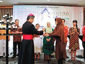 Mgr Antonius Bunjamin menyerahkan lilin kepada perwakilan umat Islam.[HIDUP/A. Aditya Mahendra]