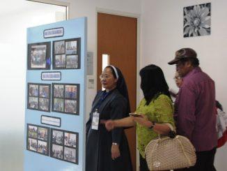 Beberapa orang menyimak foto-foto kegiatan di dalam gedung Marwita Magiswara, Bandung (HIDUP/Antonius E Sugiyanto)