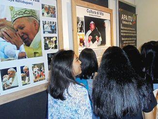 Beberapa OMK tengah menyaksikan pameran foto tematik Paus YP II di Perpustakaan USD.[HIDUP/H. Bambang S.]