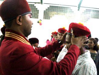 Ketua PMKRI Cabang Jakarta Pusat Yohanes Paulus Arianto Namang mengenakan topi keanggotakan kepada anggota PMKRI yang baru. [HIDUP/Steve Elu]
