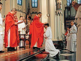 Mgr Ignatius Suharyo menumpangkan tangan dalam upacara tahbisan diakon.[HIDUP/A. Aditya Mahendra]