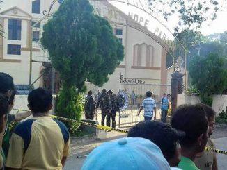 Kerumunan orang mengamati polisi ketika mereka memeriksa lingkungan di sebuah gereja Katolik di Esperanza, Filipina kota di mana sebuah bom meledak (philstar.com)