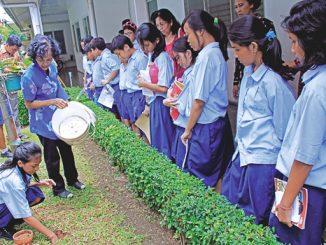 Seorang siswa Melania 2 membuat biopori disaksikan guru dan teman-temannya.[HIDUP/A.Aditya Mahendra]