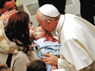 Paus Fransiskus mencium seorang bayi, korban gempa Italia Tengah di Aula Paulus VI Vatikan.[giornalettismo.com]