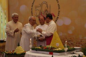 Romo Romo Stanislaus Sutopanitra SJ menerima tumpeng dari Mgr Ignatius Suharyo. (HIDUP/Edward Wirawan)