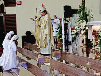 Mgr Nico menumpangkan tangan di atas kepala suster yang mengikrarkan kaul kekal.[HIDUP/Antonius E. Sugiyanto]