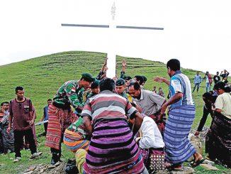 Tentara Yonif Raider 641/Beruang bersama umat menancapkan salib di Bukit Piebulak.[Romo Inosensius Nahak]